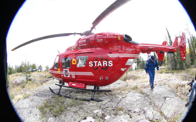 A STARS helicopter sits on a remote island in the Whiteshell.