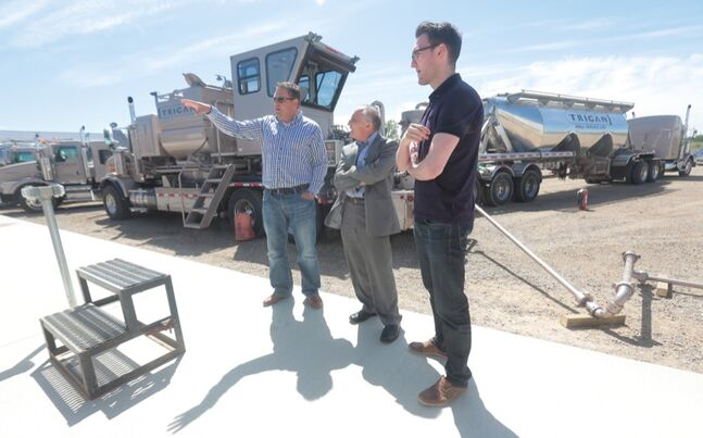 Trican Well Service's Riley Ruttan, left, and Eric Hudson, right, lead Mineral Resources Minister Dave Chomiak on a tour of their Brandon headquarters yard during Friday's grand opening of the oilpatch service company.