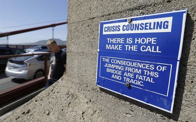 FILE - In this file photo taken Tuesday, April 30, 2013, a sign is posted above a crisis counseling call box on the Golden Gate Bridge in San Francisco. On Friday, June 27, 2014, Golden Gate Bridge officials are expected to approve a funding package for a $76 million suicide barrier. (AP Photo/Eric Risberg)