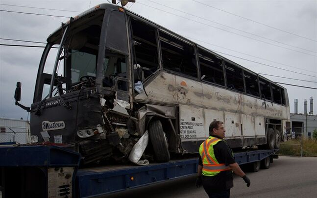 A towing company employee stands by as a tour bus that rolled over and crashed on the Coquihalla Highway south of Merritt, B.C., Thursday, is moved during an investigation at a towing company lot in Kelowna, on Friday August 29, 2014. Dozens of the 56 people on the bus were injured, seven are listed in critical condition, six others are serious and 11 have non life-threatening injuries. THE CANADIAN PRESS/Darryl Dyck