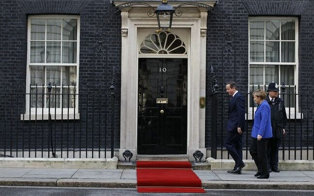 Britain's Prime Minister David Cameron walks with Germany's Chancellor Angela Merkel on the doorstep of 10 Downing Street in London, Thursday, Feb. 27, 2014. (AP Photo/Alastair Grant)