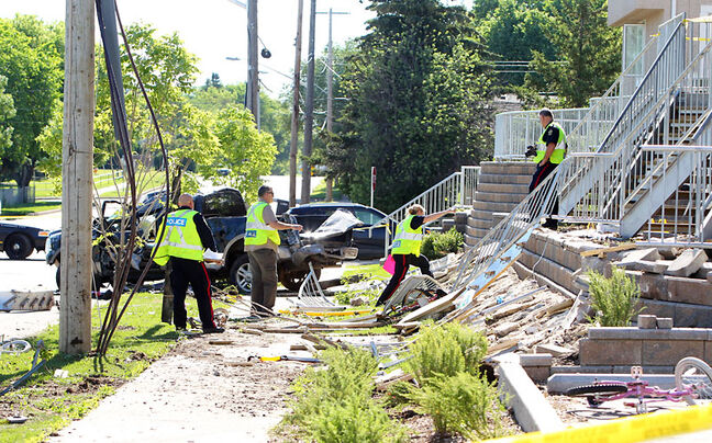 Police examine the crash scene on the 1500-block of Stickney Avenue. At about 3:45 a.m. Friday, a pickup lost control, striking a concrete embankment, hydro pole and metal stairs.