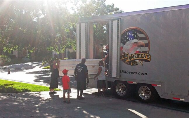 In this July 3, 2014 photo provided by Cynthia Kent, Jack Kent, age 8, watches movers load his family belongings for a move from Las Vegas to Montgomery, Ala., for a new Air Force assignment. Jack's parents rent out their home in Florida as the family moves around the nation, and they have become experienced at finding good tenants and maintaining their house from a distance. (AP Photo/Cynthia Kent)