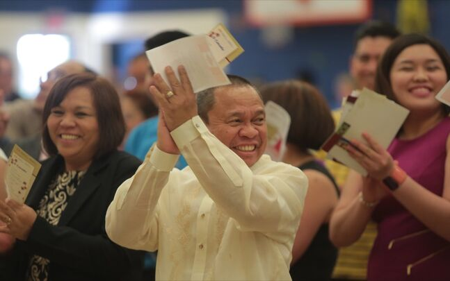 Manny Abuel claps with excitement after taking his Oath of Citizenship with his family from the Philippines during Thursday's ceremony held at Waverly Park School.