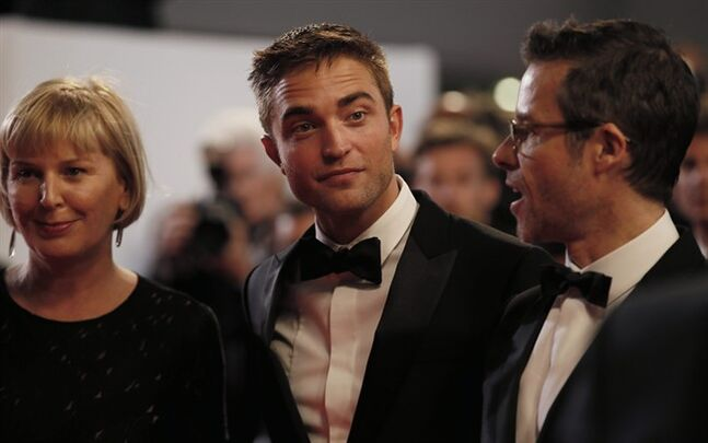 From left, producer Liz Watts, actor Robert Pattinson and actor Guy Pearce pose for photographers as they arrive for the screening of The Rover at the 67th international film festival, Cannes, southern France, Sunday, May 18, 2014 (AP Photo/Alastair Grant)