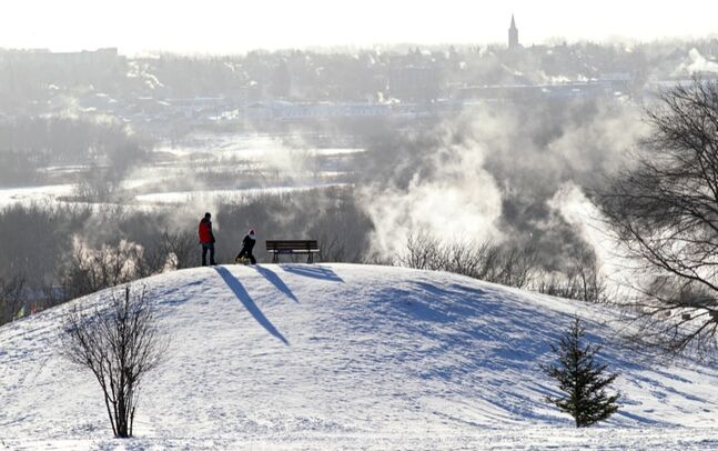 Adrian Boggs and his six-year-old daughter Danika stand at the top of Hanbury Hill while braving the cold and sledding on Monday. In the background smoke rises from Brandon buildings. The city is keeping the lights on at Hanbury Hill until 1 a.m. on New Year's Eve. The skating oval will also be open until 1 a.m.