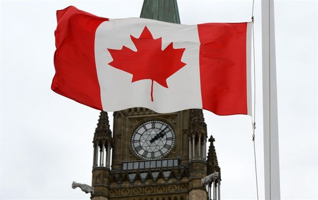 A Canadian flag blows in front of the Peace Tower on Parliament Hill in Ottawa, Ont., Wednesday, Oct. 24, 2012. Two items often held up as cornerstones of Canadian values -- the Charter of Rights and Freedoms and universal health care -- are tops among things that help unite the country, according to respondents to a new poll. THE CANADIAN PRESS/Sean Kilpatrick