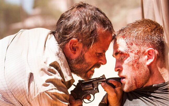 This image released by A24 Films shows Guy Pearce, left, and Robert Pattinson in a scene from