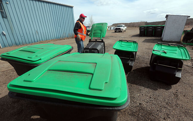 Summer employee Chris Sitko assembles new composting bins at the Eastview Landfill on Wednesday afternoon. The new bins are being put into service throughout Brandon, and are proving more popular as the second season of the city's green cart program gets underway.