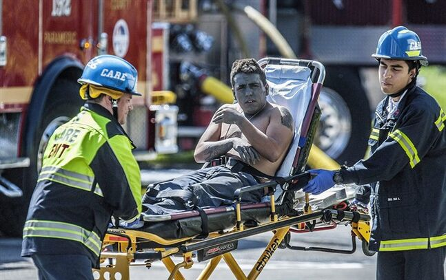 An injured worker is moved toward a waiting ambulance after an explosion was reported at a business in La Habra, Calif., Tuesday, April 29, 2014. Authorities say eight people have been hurt, three critically, in an explosion and fire at a commercial building in south Los Angeles County. (AP Photo/The Orange County Register, Bruce Chambers)