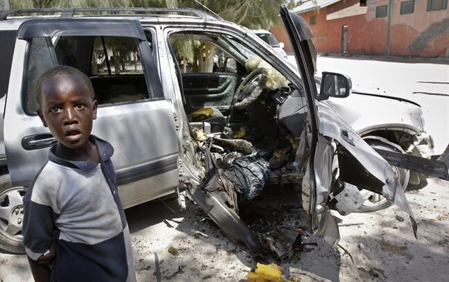 A boy observes the wreckage of a car bomb attack against the Keysaney Hospital, which is run by the International Committee of the Red Cross (ICRC), in the capital Mogadishu, Somalia Wednesday, June 18, 2014. A nurse says the car bomb detonated outside of the Keysaney hospital killing two people, a doctor and a nurse, and wounded others at the 65-bed emergency care hospital which has been operational for much of the last two decades of conflict in Somalia, making it one of the city's most important health facilities. (AP Photo/Farah Abdi Warsameh)