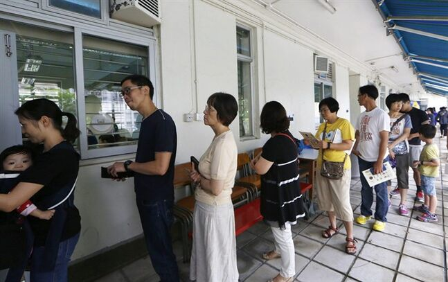 People queue up at a polling station on the last day to vote for an unofficial referendum on democratic reform in Hong Kong Sunday, June 29, 2014. More than half a million Hong Kongers have voted in an unofficial referendum on democratic reform in the specially administered Chinese city that Beijing has blasted as illegal. About 700,000 ballots have been cast since voting started from June 20, most of them online or through a smartphone app. (AP Photo/Kin Cheung)