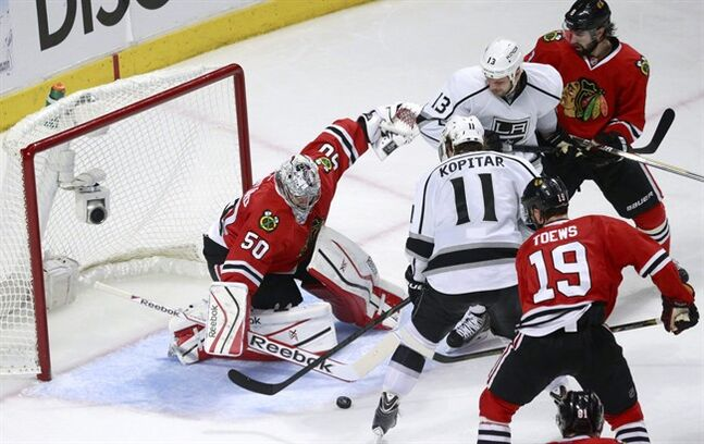 Chicago Blackhawks goalie Corey Crawford (50) clears the puck away from Los Angeles Kings center Anze Kopitar (11) and Kings' Kyle Clifford (13) as Chicago's Nick Leddy (8) and Jonathan Toews (19) watch during the second period of Game 2 of the Western Conference finals in the NHL hockey Stanley Cup playoff,s Wednesday, May 21, 2014, in Chicago. (AP Photo/Charles Rex Arbogast)