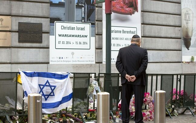 A man stops to pay his respects prior to a service for the victims of a shooting at the Jewish Museum in Brussels, on Monday, June 2, 2014. Police have arrested a suspect after three people were killed and one seriously injured in a spree of gunfire at the Jewish Museum in Brussels on Saturday, May 24, 2014. (AP Photo/Virginia Mayo)