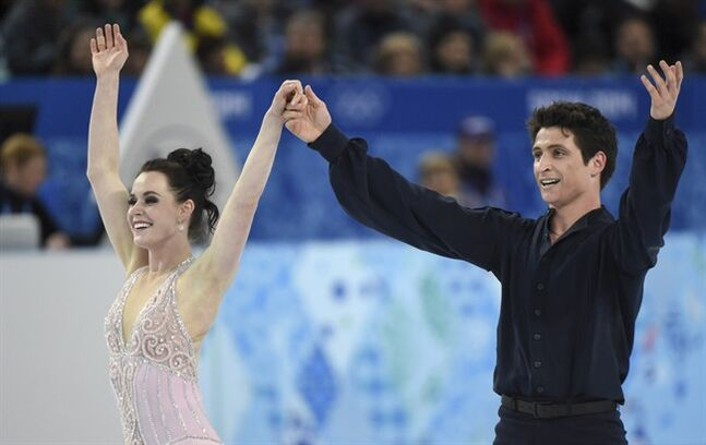 Canada's Tessa Virtue and Scott Moir salute the crowd following their free dance in the ice dance competition at the Sochi Winter Olympics Monday, February 17, 2014 in Sochi. THE CANADIAN PRESS/Paul Chiasson