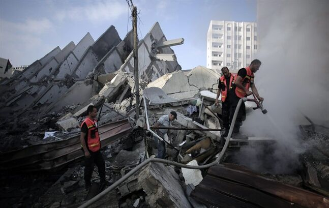 FILE - In this Tuesday, Aug. 26, 2014 file photo, Palestinian firefighters extinguish a fire in the rubble of the destroyed 15-story Basha Tower, following early morning Israeli airstrikes in Gaza City. Shelter Cluster, chaired by the Norwegian Refugee Council with the participation of the U.N. refugee agency and the Red Cross, an international organization involved in assessing post-conflict reconstruction, said in a report issued late Friday, Aug 29, 2014, it will take 20 years under current levels of restrictions to rebuild the Gaza Strip's battered and neglected housing stock following the war between Hamas and Israel. (AP Photo/Khalil Hamra, File)