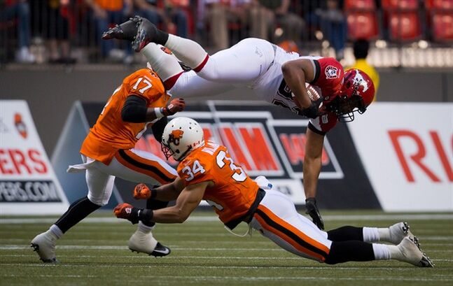 Calgary Stampeders' Nik Lewis, top, is upended by B.C. Lions' Torri Williams (34) after catching a pass during the first half of a pre-season CFL football game in Vancouver, B.C., on Friday June 20, 2014. The gold-wrapped TV deal the CFL secured last year will make financial life a lot easier for every franchise this season.But for a few weeks this spring, it also played a significant role in a labour dispute that could have stopped the season from getting off the ground.THE CANADIAN PRESS/Darryl Dyck