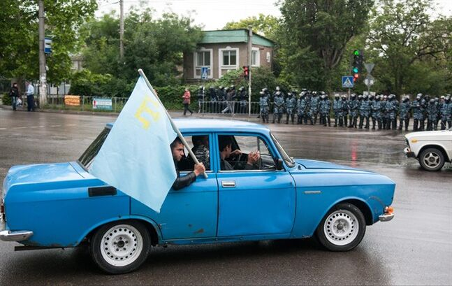 Crimean Tatars hold a flag with their movement's emblem on it driving through the city of Simferopol, Crimea, Sunday, May 18, 2014. Crimean Tatars gathered for a rally commemorating the 70th anniversary of Stalin's mass deportation. (AP Photo/Alexander Polegenko)