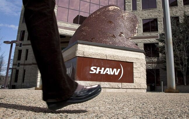 A pedestrian walks past the headquarters of Shaw Communications in Calgary, April 13, 2011. THE CANADIAN PRESS/Jeff McIntosh