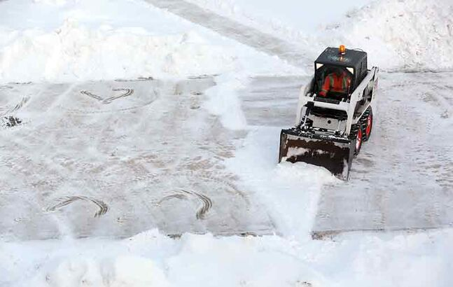 A Bobcat loader was used to clear the snow from the sidewalks at Brandon University on Monday.