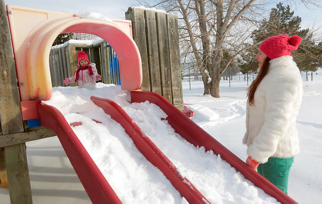 Kylie Kovalenko looks out from the top of the slide for her mother Marina Kovalenko during an afternoon of play at Queen Elizabeth Park on Monday. Despite some cool winds and snow in the next few days, outside playtime should be pretty spectacular by the weekend.