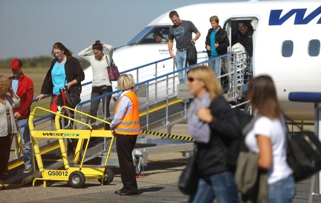 Brandon Sun Passengers disembark from a WestJet flight from Calgary two weeks from after the first flight landed in Brandon in September 2013.