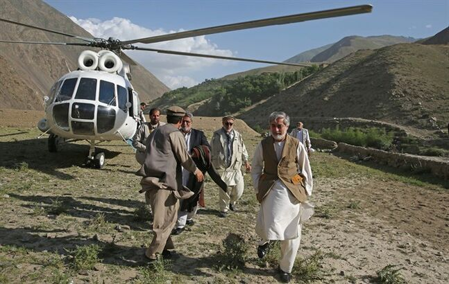 Afghanistan's presidential candidate Abdullah Abdullah, right, arrives for a visit of flood affected area in Guzirga i-Nur district of Baghlan province, Afghanistan, Sunday, June 8, 2014. Abdullah Abdullah, the front runner in Afghanistan's June 14 presidential runoff election visited the area Sunday.(AP Photo/Massoud Hossaini, Pool)
