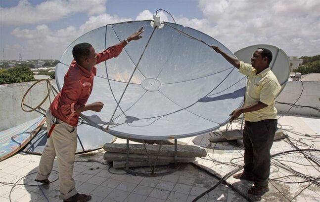 In this photo taken Monday, Aug. 4, 2014, a technician from Access TV, a new Somali satellite television company offering world news, local news and sports, adjusts the signal on a satellite dish at the company's headquarters in Mogadishu, Somalia. The TV business is booming in Somalia, in part because of fears by people of gathering in public places like movie theaters, hotels and restaurants that are targeted for deadly attacks by the al-Qaida-linked militant group al-Shabab. (AP Photo/Farah Abdi Warsameh)