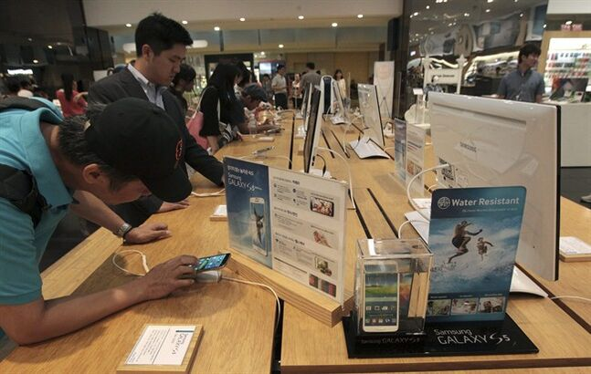 Visitors try out Samsung Electronics Co.'s Galaxy 5 at the company's showroom in Seoul, South Korea, Tuesday, July 8, 2014. Samsung Electronics Co. said operating profit declined to a two-year low in the second quarter, hit by the strong local currency and slowing demand for smartphones in China. (AP Photo/Ahn Young-joon)