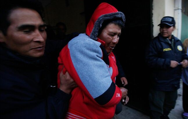 Javier Cusi Aduviri, center, is escorted by Bolivian police officers at the police station in El Alto, Bolivia, Thursday, June 26, 2014. An emotionally disturbed Cusi Aduviri wielding a kitchen knife went on a rampage in the terminal of the La Paz international airport on Thursday, stabbing 11 people, authorities said. Deputy Interior Minister Jorge Perez said the attacker told police he