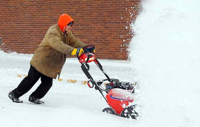 Wendy's employee Jesse Kendel uses a snowblower to clear the restaurant parking lot after a Colorado low blanketed the Wheat City in snow on Saturday.