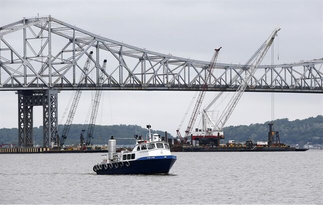 A boat makes it's way up the Hudson River north of the Tappan Zee bridge, under construction in Tarrytown, N.Y., Wednesday, May 28, 2014. As part of a condition of constructing the new bridge, the New York State Department of Environmental Conservation has required the state Thruway Authority to track and study federally endangered sturgeon that live in the river near the bridge. Scientists are tagging and tracking sturgeon using surgically implanted electronic tracking devices to study whether the bridge construction affects their behavior or reproductive life cycles. (AP Photo/Kathy Willens)