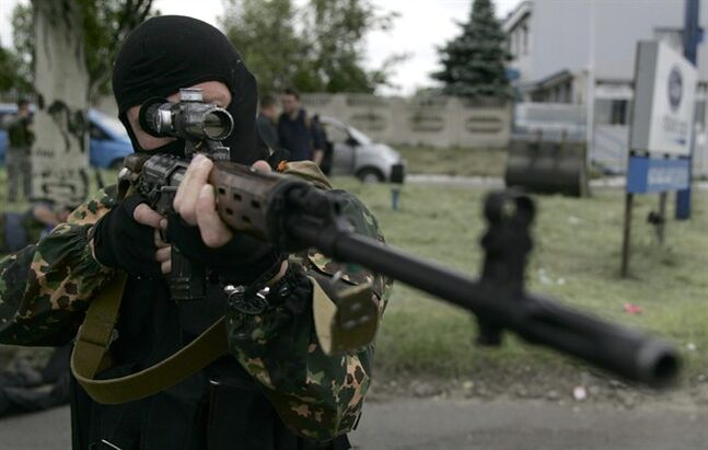 A Pro-Russian militia man poses aiming his sniper rifle in Donetsk, eastern Ukraine, on Friday, May 23, 2014. At least three people died when Ukrainian national guard unit and pro-Russian militiamen fought in the village of Karlivka early Friday. (AP Photo/Alexander Ermochenko)