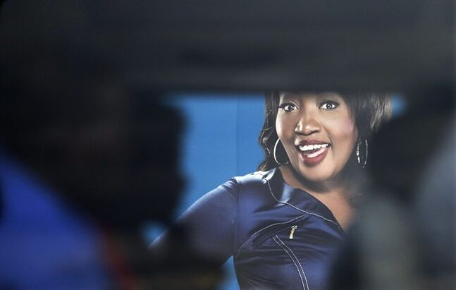 A taxi with passengers drives past a billboard featuring Sophie Ndaba, an actor who played the Queen Moroka character in