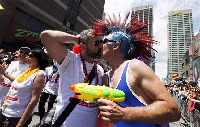 Paraders kiss during the 33rd annual Pride Parade in Toronto on June 30, 2013. THE CANADIAN PRESS/Michelle Siu