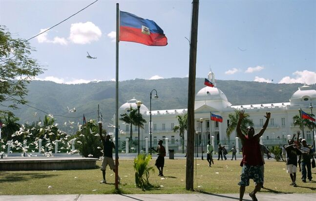 Supporters of Haitian President Jean-Bertrand Aristide protest outside the presidential palace in Port-au-Prince, Haiti after the coup d'etat, Sunday, Feb. 29, 2004. THE CANADIAN PRESS/AP, Ricardo Mazalan