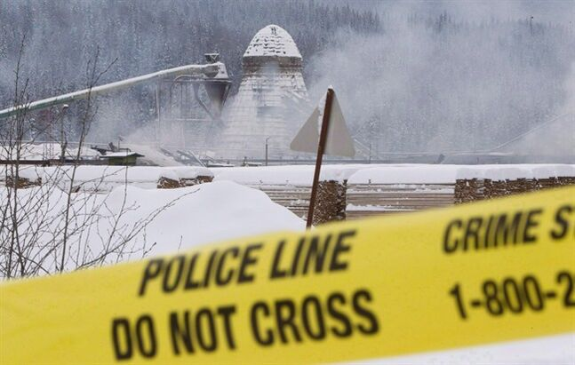 Smoke rises as police tape surrounds Abine Forest Products mill in Burns Lake, B.C. in a Jan. 21, 2012 file photo. THE CANADIAN PRESS/Jonathan Hayward