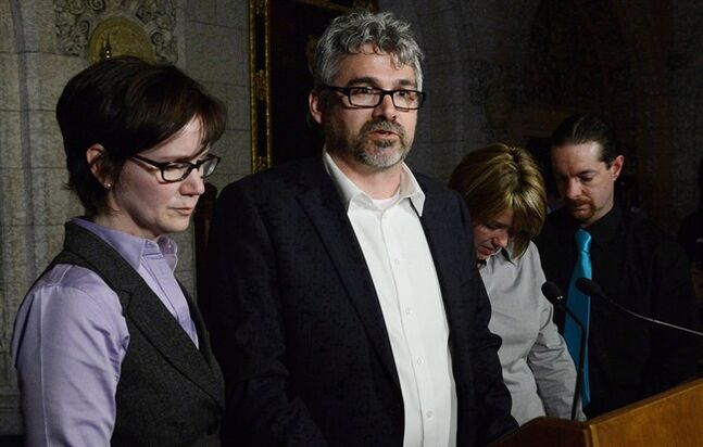 Rehtaeh Parson's father Glen Canning, second from left, and wife his Krista speak to reporters as Leah Parsons, second from right, mother of Parsons and her partner Jason Barnes look on in the foyer of the House of Commons on Parliament Hill in Ottawa on April 23, 2013. A man pleaded not guilty Friday to charges of uttering threats and criminal harassment in a case involving the father of Rehtaeh Parsons. Police have not publicly disclosed the name of the alleged victim, but Glen Canning, Parsons' father, says the charges relate to online threats he alleges were made against him last year. THE CANADIAN PRESS/Sean Kilpatrick