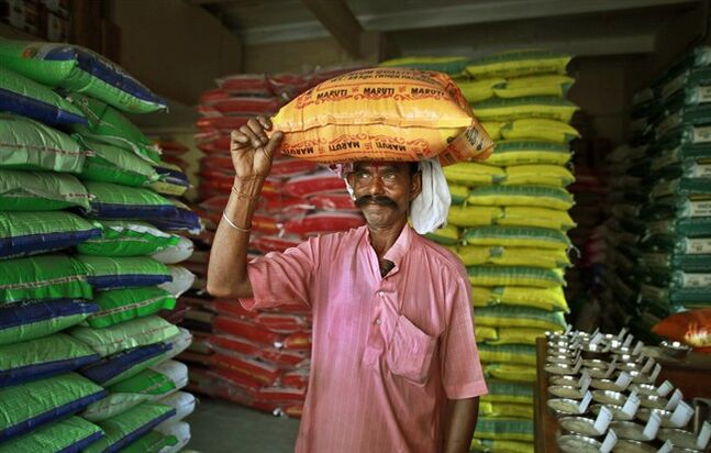 An Indian laborer carries a sack of rice at a shop in Gauhati, India, Thursday, July 10, 2014. THE CANADIAN PRESS/AP, Anupam Nath