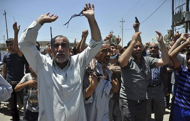 In this June 23, 2014, photo, mourners chant slogans against the al-Qaida breakaway group Islamic State of Iraq and the Levant after they bury 15 bodies in the village of Taza Khormato near the northern oil-rich city of Kirkuk, Iraq. U.S. teams of special forces going into Iraq after a three-year gap will face an aggressive insurgency, a splintering military and a precarious political situation as they help Iraqi security forces improve their ability to battle Sunni militants. (AP Photo/Emad Matti)