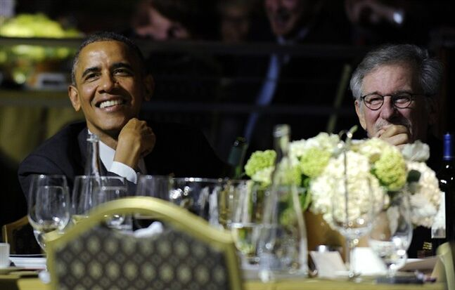 President Barack Obama, left, sits next to movie director Steven Spielberg, right, as they listen to Conan O'Brien during the USC Shoah Foundation's 20th anniversary Ambassadors for Humanity gala in Los Angeles, Thursday, May 8, 2014. Obama received an award from the foundation created by Spielberg and is spending three days in California where he plans to raise money for the Democratic Party. (AP Photo/Susan Walsh)