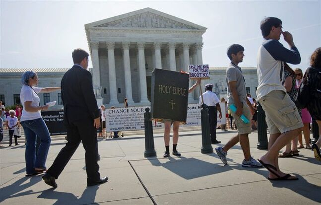 A demonstrator dressed as the 'Bible' stands outside the Supreme Court in Washington, Monday, June 30, 2014, awaiting the court's decision on the Hobby Lobby case. The Supreme Court says corporations can hold religious objections that allow them to opt out of the new health law requirement that they cover contraceptives for women.(AP Photo/Pablo Martinez Monsivais)