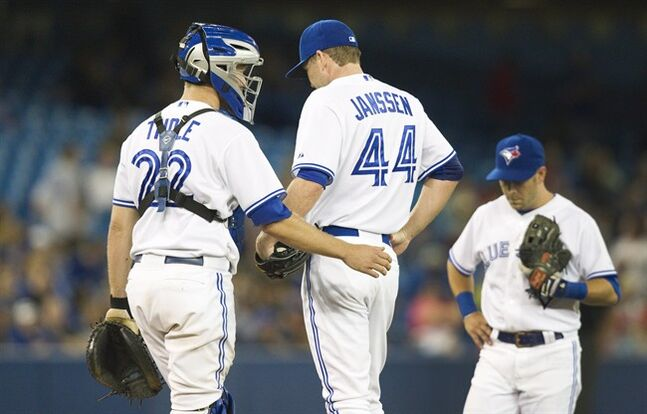 Toronto Blue Jays catcher Josh Thole goes out to talk to pitcher Casey Janssen with Jays third baseman Steve Tolleson after Janssen gave up three runs and the lead to the Detroit Tigers in the ninth inning of their AL baseball game in Toronto Friday August 8, 2014. THE CANADIAN PRESS/Fred Thornhill