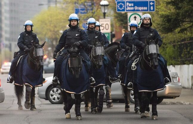 Police on horse back move along a street during an anti-capitalist demonstration in Montreal, Tuesday, May 1, 2012. A police horse was briefly on the loose in Montreal Saturday afternoon after it escaped from its handler and began galloping through the city streets.THE CANADIAN PRESS/Graham Hughes