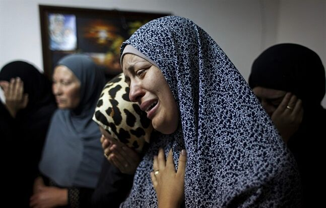 Female relatives of slain Palestinian Ahmad Arafat Sabarin, 20, who was killed by Israeli army fire early Monday during a confrontation between stone throwers and soldiers, cries with a relative at the family house, prior to his funeral procession in the Palestinian refugee camp of Jalazoun, at the outskirts of the West Bank city of Ramallah, Monday, June 16, 2014. Israeli troops on Monday rounded up dozens more senior Hamas activists and killed a Palestinian in a clash with stone throwers — part of a feverish search for three kidnapped Israeli teenagers who Israel alleges were seized by the Islamic militant group. (AP Photo/Nasser Nasser)