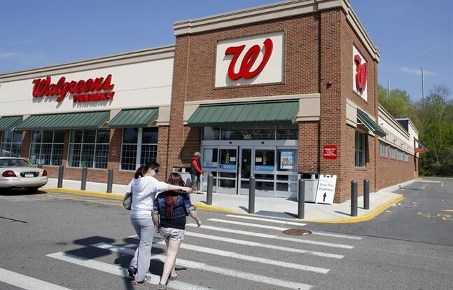 In this Wednesday, May 14, 2014 photo, customers walk toward an entrance to a Walgreens store location, in Boston. Walgreen Co. reports quarterly earnings on Tuesday, June 24, 2014. (AP Photo/Steven Senne)