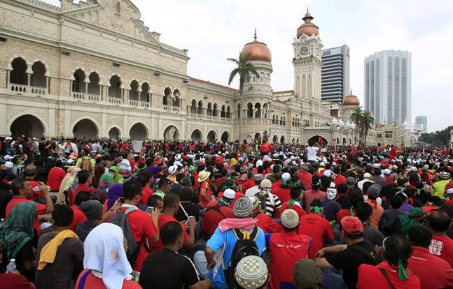 Protesters sit in front of the historical building of Sultan Abdul Samad during a protest against the implementation of the Goods and Services Tax (GST) in Kuala Lumpur, Malaysia, Thursday, May 1, 2014. (AP Photo/Lai Seng Sin)