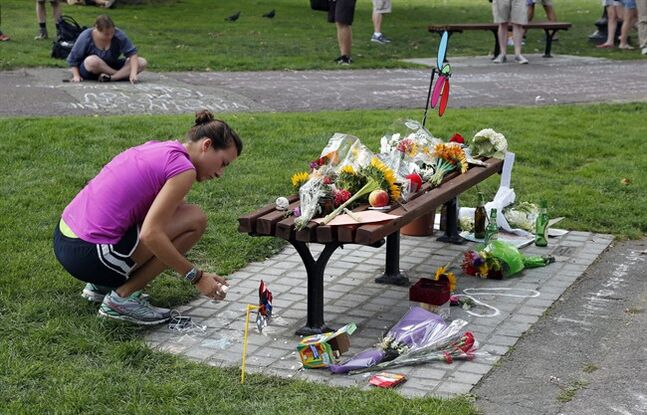 Women write messages with chalk near a bench at Boston's Public Garden, Tuesday, Aug. 12, 2014, where a small memorial has sprung up at the place where Robin Williams filmed a scene during the movie,
