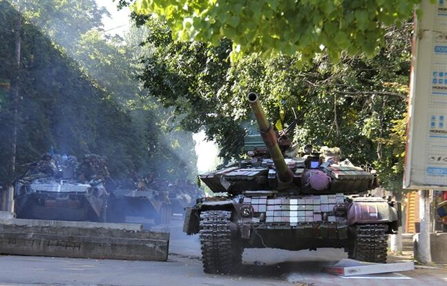 In this photo taken on Saturday, July 5, 2014, Ukrainian soldiers aboard armored vehicles pass a barricade in downtown Slovyansk, eastern Ukraine. After Ukrainian forces' seizure of a key rebel stronghold in the east, the major cities of Donetsk and Luhansk could be the next focus of major fighting. Three bridges on roads leading to Donetsk were blown up Monday — possibly to hinder military movements, though the rebels claim it was the work of pro-Kiev saboteurs. (AP Photo)
