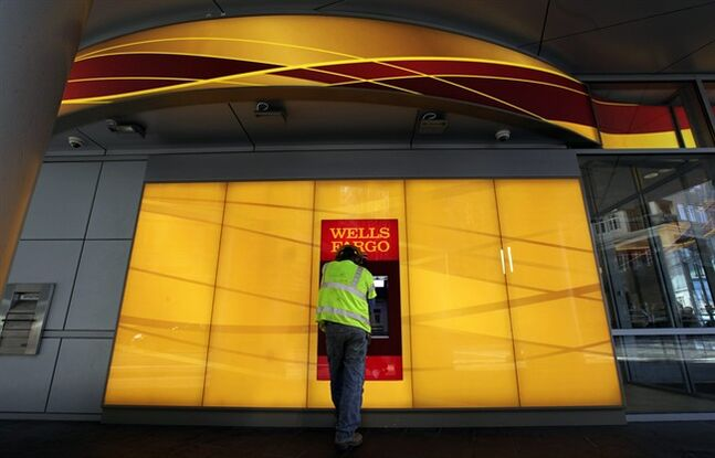 FILE - In this Jan. 17, 2012, file photo, a customer uses an ATM outside a Wells Fargo branch in Charlotte, N.C. Wella Fargo & Co. reports quarterly results before the market opens on Tuesday, Jan. 14, 2014. (AP Photo/Chuck Burton, File)